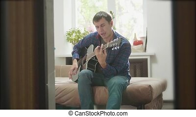 man playing music by wooden acoustic guitar. Man Playing Acoustic Guitar Close Up slow motion video. in the room lifestyle sits on the couch. man and guitar concept