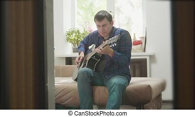 man playing music by wooden acoustic guitar. Man Playing Acoustic Guitar Close Up slow motion video. in the room sits on the couch. man and guitar concept lifestyle