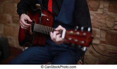 man playing on a 6-string acoustic guitar