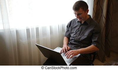 man playing on a laptop in the room