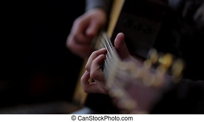 Man playing on acoustic guitar.