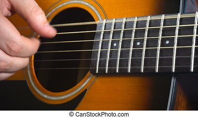 Man playing on acoustic guitar. Closeup video of hand and...