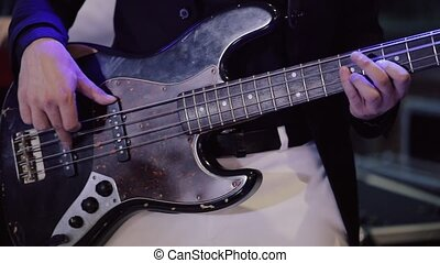 Man Playing on Bass Electric Guitar