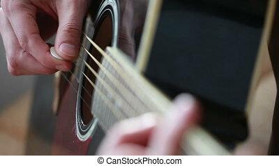 man playing on black guitar. mediator