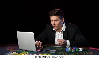 Man playing online poker at a table. Close up