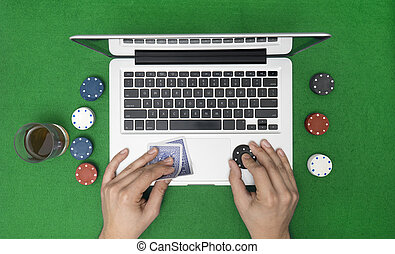 Man playing online poker with laptop on a green table with chips,