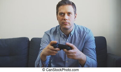 Man playing racing video game on TV. Gamepad controller in...
