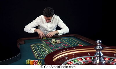 Man playing roulette wins at the casino. Black