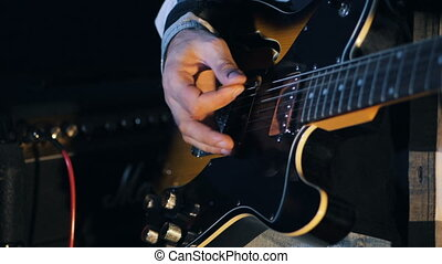 man playing the electric guitar at the concert. Close up view of guitarist plays electro guitar in dark room. Slowmotion