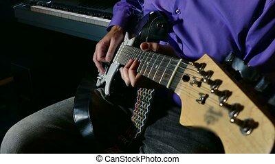man playing the electric guitar recording studio