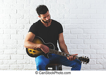 Man playing the guitar - Portrait of attractive caucasian...