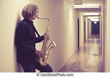 Man playing the saxophone in a hallway - Photo of a young...