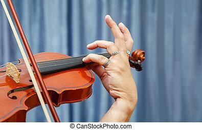 man playing the violin. hands closeup