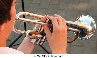 man playing trumpet march music sitting on sunny summer day