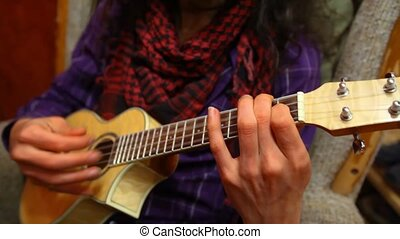 Close up of guitarist with long hair wearing red scarf and purple shirt, playing ukulele sitting in a sofa in his living room - traveling up