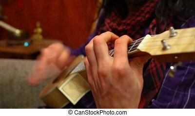 Man playing ukulele in living room. - Close up of guitarist ...