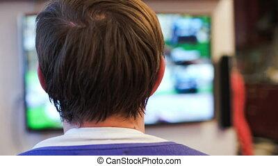 Man playing video game - Back close-up shot of man being...
