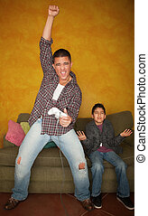 Man Playing Video Game with Bored Young Boy