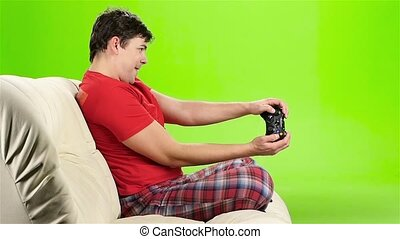 Man playing videogames with gamepad sitting on couch. Slow motion