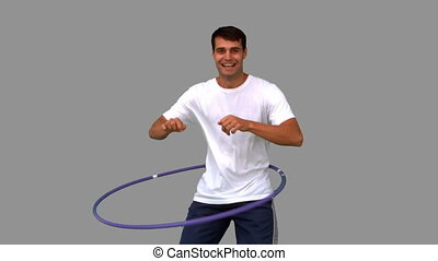 Man playing with a hula hoop on grey screen