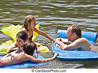 Man Playing with Children in Water - A man playing and...