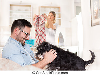 Man playing with dog and woman doing housework