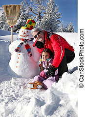 Man playing with his granddaughter in the snow