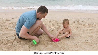 Man playing with infant in sand