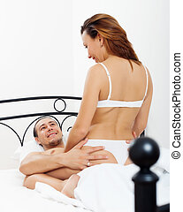 man playing with woman in bed