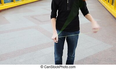 man playing with yoyo professionally on bridge - young man...