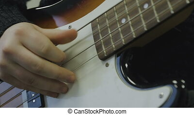 Man plays bass guitar close-up