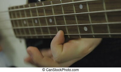 Man plays bass guitar close-up