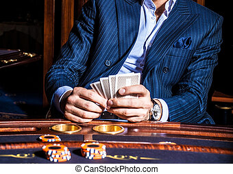 Man plays cards in casino - Man in blue classical suit plays...