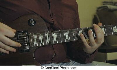 Man plays electric guitar, hands close-up