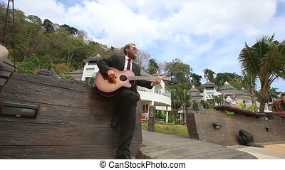 man plays guitar by wall and goes out along bridge - bearded...