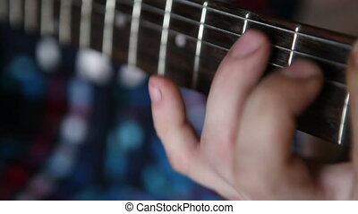 man plays guitar, his fingers on the fretboard