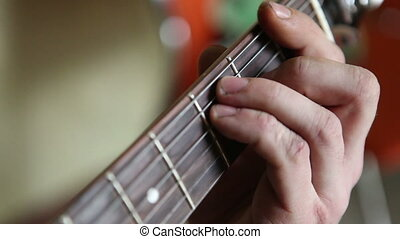 man plays guitar, his fingers on the fretboard closeup