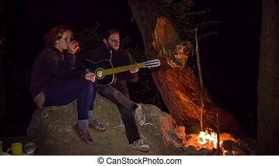 man plays guitar to his girl at night
