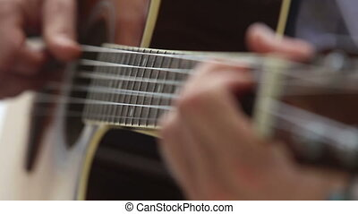 man plays guitar with focus moving along neck - european man...