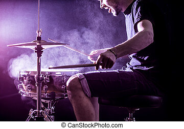 man plays musical percussion instrument with sticks, a...