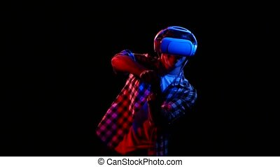 Man plays on gamepad in virtual reality glasses. Red light