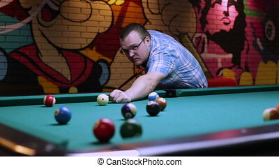 Man plays pool, man driving the ball in the hole