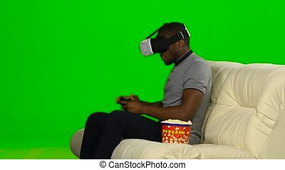 Man plays the game in a VR mask with a joystick. Green...
