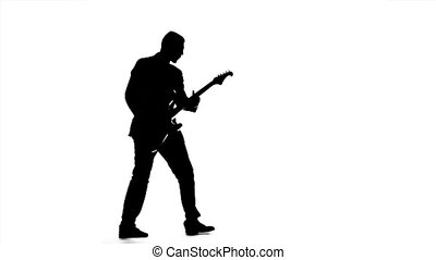Man plays the melody on the guitar. Silhouette. Slow motion