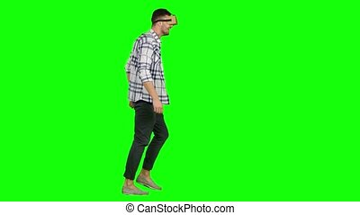 Man plays virtual augmented reality game using head mounted display, virtual reality game, man with pleasure uses head-mounted display, man in a virtual reality mask looks around, manipulates his surroundings. and walking, with a virtual reality head set, on green screen
