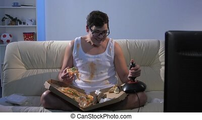 Man plays with a joystick and eating pizza