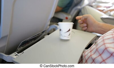 man plays with coffee Cup on the plane. man traveler sitting in passenger compartment.
