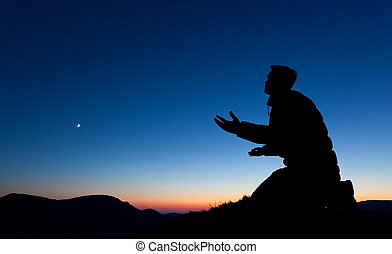 Man pleading to God on the summit of a mountain at sunset with the moon in the sky.