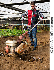 Man plowing ground with cultivator - Young man plowing ...