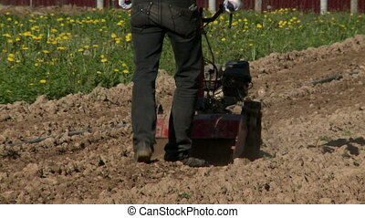Man plowing land by agricultural cultivator on a sunny day